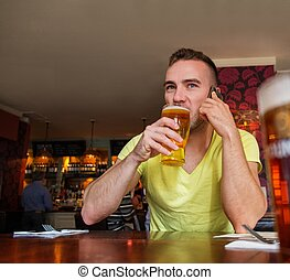 Handsome young man with mobile phone and beer in a pub
