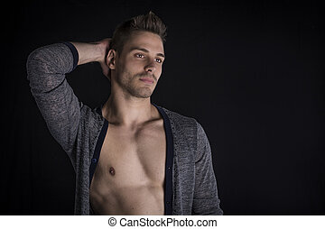 Handsome young man with open sweater on naked chest.