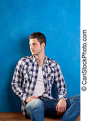 handsome young man with plaid shirt sitting on wood