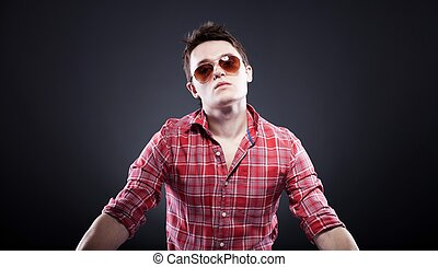 Handsome young man with sunglasses on dark background -...