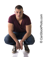Handsome young man with t-shirt and jeans sitting on his heels
