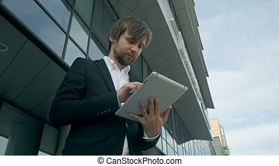 Handsome young man with tablet in the streets near office