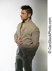 Handsome young man with wool sweater on light background