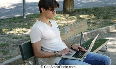 Handsome young man working at computer in park