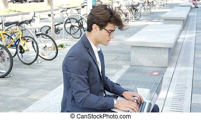 Handsome young man working at computer outdoor - Handsome...