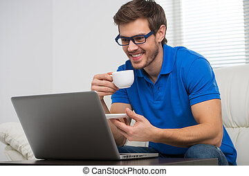 handsome young man working on computer laptop at home. happy guy looking at screen and holding cup