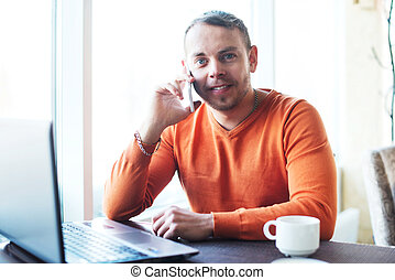 Handsome young man working with notebook, talking on the phone, smiling, looking at camera, while enjoying coffee in cafe