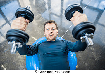 Handsome young man workout with dumbbells on fitness ball at gym