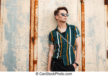 Handsome young model man with a hairstyle with sunglasses in a fashion beach shirt with a bag stands near a metal wall on the street