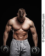 Handsome young muscular man exercising with dumbbells