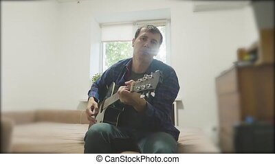 Handsome young musician playing the guitar and singing. Man Playing Acoustic Guitar Close Up slow motion video. in the room sits lifestyle on the couch. man and guitar concept