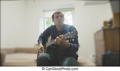 Handsome young musician playing the guitar and singing. Man Playing Acoustic Guitar Close Up slow motion video. in the room sits on lifestyle the couch. man and guitar concept