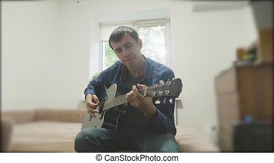 Handsome young musician playing the guitar and singing. Man Playing Acoustic Guitar Close Up slow motion video. in the room sits on the couch. man and guitar concept lifestyle