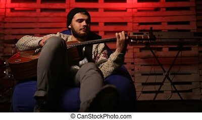 Handsome young musician playing the guitar