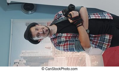 Handsome young photographer in hat holding camera and smiling in modern studio photo shoot. There are skyscrapers in the background. Video with Vertical Screen Orientation 9:16