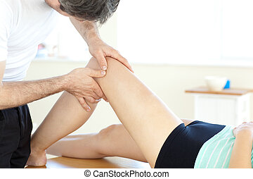 Handsome young physical therapist giving a leg massage in a ...