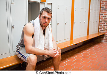 Handsome young sports student sitting on a bench with a...