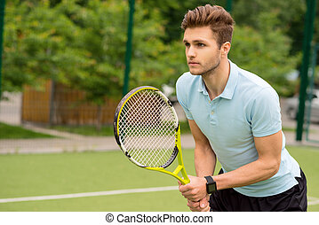 Handsome young sportsman playing tennis