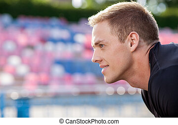 Handsome young sportsman takes breath after running