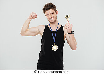 Handsome young sportsman with medal and reward