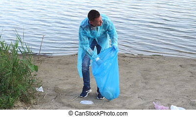Handsome young volunteer with team gathering garbage on river bank.