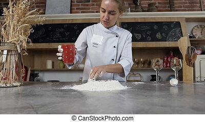 Handsome young woman pouring water into the flour. Inscription on apron, model name Nina Leus