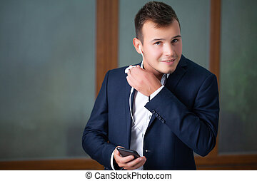Handsome young worker uses a telephone in the company office