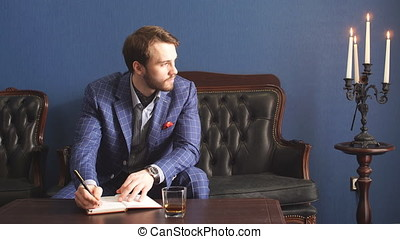 Handsome young writer in a classy suit having an inspiration...