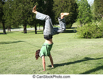 Teen boy doing hand stand on pretty lawn. Shot with Canon 20D.