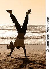 Handstand - Dog watching a boy doing handstand on the beach