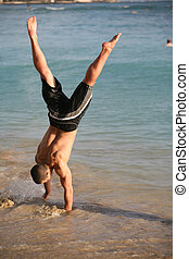 Handstand on the beach - Young man doing handstand on the ...