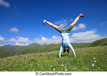 handstand woman have fun in a mountain peak meadow
