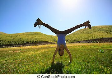 handstand young fitness woman on grassland meadow