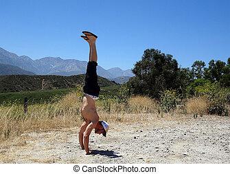 Handstanding in Dirt Field in California with Mountain in...