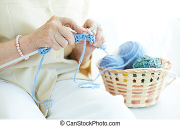 Handwork - Hands of elderly woman knitting woolen clothes
