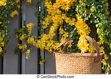 Handwoven beautiful wicker handbag with fresh yellow flowers...