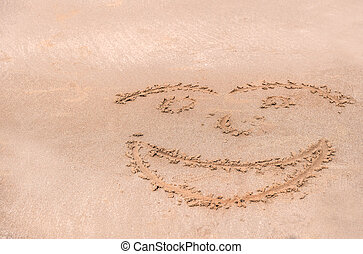 Handwrite face on the sand at the beach