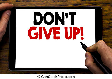 Handwriting Announcement text showing Don t Give Up. Business concept for Motivation Determination, Written on tablet laptop, wooden background with businessman hand, finger writing on PC.