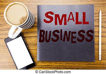 Handwriting Announcement text showing Small Business. Business concept for Family Owned Company Written on notepad note paper, wooden wood background with coffee pen and cellphone phone