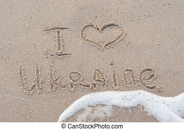 Handwriting I love Ukraine on the sandy beach