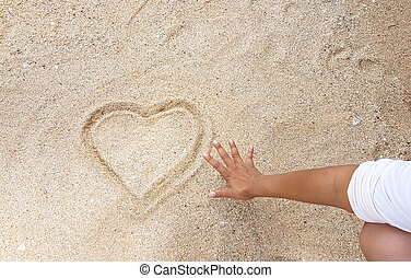 handwriting of heart on golden sand with reach out of hand