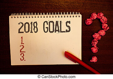 Handwriting text 2018 Goals 1. 2. 3.. Concept meaning Resolution Organize Beginnings Future Plans Reddish paper balls structures question mark red pen notebook browny desk.