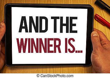 Handwriting text And The Winner Is . Concept meaning Announcing as first place in competition or race Hand hold showing colorful letters black marker red pen timber carrel.