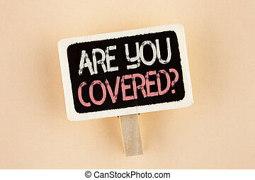 Handwriting text Are You Covered Question. Concept meaning Health insurance coverage disaster recovery written on Wooden Notice Board on the plain background.