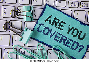 Handwriting text Are You Covered Question. Concept meaning Health insurance coverage disaster recovery written on Sticky Note paper placed on White Keyboard Clips and Paper Pins next to it.
