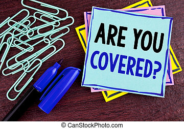 Handwriting text Are You Covered Question. Concept meaning Health insurance coverage disaster recovery written on Sticky Note Paper on wooden background Marker and Paper Clips next to it.