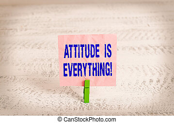 Handwriting text Attitude Is Everything. Concept meaning Personal Outlook Perspective Orientation Behavior Green clothespin white wood background colored paper reminder office supply.
