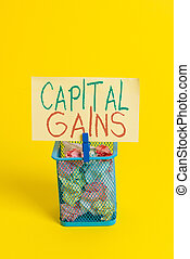 Handwriting text Capital Gains. Concept meaning Bonds Shares Stocks Profit Income Tax Investment Funds Trash bin crumpled paper clothespin empty reminder office supplies yellow.