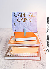 Handwriting text Capital Gains. Concept meaning Bonds Shares Stocks Profit Income Tax Investment Funds pile stacked books notebook pin clothespin colored reminder white wooden.