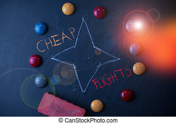 Handwriting text Cheap Flights. Concept meaning costing little money or less than is usual or expected airfare Round Flat shape stones with one eraser stick to old chalk black board.